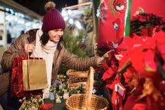 Meisje die bloemensamenstelling kiezen bij Kerstmismarkt stock afbeelding