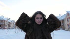 Meisje die in Bontjas in de Winterdorp lopen stock videobeelden