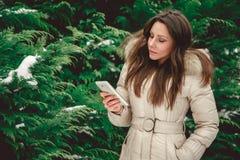 Meisje die in bos telefoon ernstig bekijken Royalty-vrije Stock Foto's