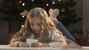 Meisje die brief zetten aan Kerstman in envelop, geloof in Kerstmismirakel stock videobeelden