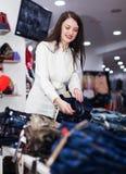 Meisje die broeken kiezen bij markt Stock Afbeeldingen