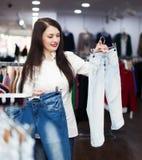 Meisje die broeken kiezen bij opslag Stock Fotografie