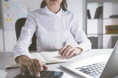 Meisje die calculator in bureau gebruiken Stock Fotografie