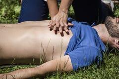 Meisje die cardiopulmonale reanimatie maken aan een onbewuste kerel na hartaanval stock afbeeldingen