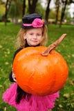 meisje die in Carnaval-kostuum met pompoen Halloween vieren stock afbeelding