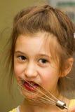 Meisje die chocolade likken van de mixerklopper na het mengen van deeg voor verjaardagscake Tolerant ouderschap, het leren royalty-vrije stock afbeelding