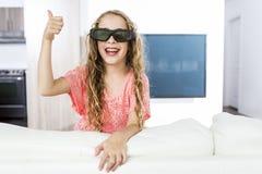 Meisje die 3D glazen dragen en op televisie letten Stock Fotografie