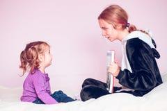 Meisje die de beelden in een boek haar jongere zuster tonen Stock Foto's