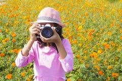 Meisje die de camera in bloementuin houden stock foto's
