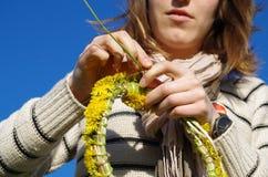 Meisje die de ketting van het bloemmadeliefje maken royalty-vrije stock fotografie