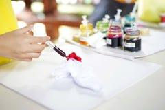 Meisje die de kleur op het stuk van witte doek laten vallen Vakmanschap en workshopconcept stock foto