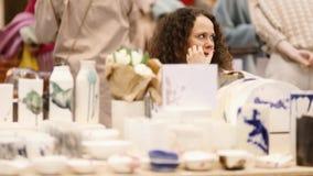 Meisje die de met de hand gemaakte teller van de keramiekmarkt verkopen stock video