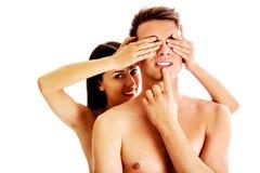 Meisje die de ogen van haar vriend voor een geïsoleerde verrassing behandelen - Royalty-vrije Stock Afbeelding