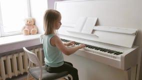 Meisje die de piano bestuderen thuis te spelen Peuterkind die pret met het leren hebben om muziekinstrument te spelen stock video