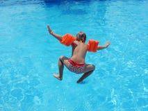 Meisje die in de pool springen Stock Afbeeldingen