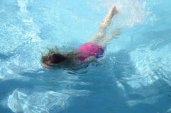 Meisje die in de pool zwemmen stock foto's