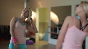 Meisje die in de spiegel in de gymnastiek kijken stock video