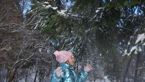 Meisje die de tak van pijnboomboom schudden die door sneeuw wordt behandeld De tiener is gekleed in een roze gebreide hoed en vui stock video