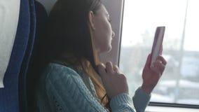 Meisje die de telefoon onderzoeken als spiegel voor het ombing van haar haar tijdens het reizen op spoorweg Mooie vrouwenritten o stock videobeelden