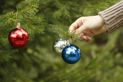 Meisje die decoratieve stuk speelgoed bal op Kerstboomtak hangen Royalty-vrije Stock Afbeeldingen