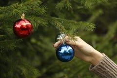 Meisje die decoratieve stuk speelgoed bal op Kerstboomtak hangen Stock Foto