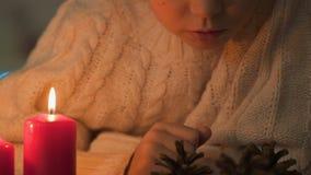 Meisje die denneappels, kaars dichtbij het branden bekijken, de close-up van Kerstmisambachten stock footage