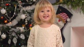 Meisje die dichtbij de Kerstboom glimlachen stock video