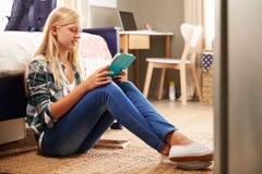 Meisje die digitale tablet in haar slaapkamer gebruiken Stock Foto