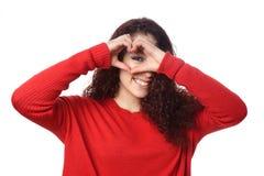 Meisje die door de handteken van de hartvorm gluren Stock Afbeeldingen
