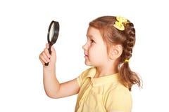 Meisje die door een vergrootglas kijken stock foto's