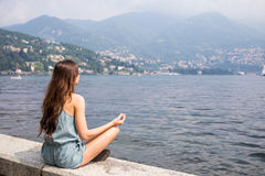 Meisje die door het meer mediteren Stock Foto