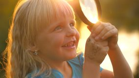 Meisje die door meer magnifier zonsondergang bekijken stock videobeelden