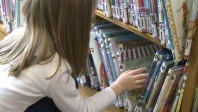 Meisje die door rijen van de boeken van kinderen kijken stock footage