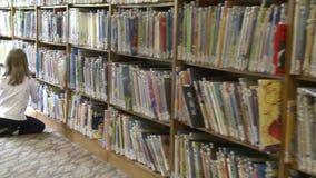 Meisje die door rijen van de boeken van kinderen kijken stock video