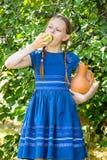 Meisje die een appel in een de zomertuin eten royalty-vrije stock afbeelding