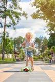 Meisje die een autoped berijden bij het park Stock Afbeeldingen