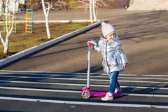 Meisje die een autoped in het Park berijden op een Zonnige de lentedag Actieve vrije tijd en openluchtsport voor kinderen stock foto