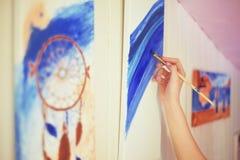 Meisje die een beeld in huisstudio schilderen Modelvrouw die haar beeld schilderen Art De vrouw trekt verven Meisje belast met cr stock afbeelding