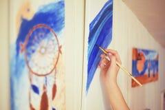 Meisje die een beeld in huisstudio schilderen Modelvrouw die haar beeld schilderen Art De vrouw trekt verven Meisje belast met cr royalty-vrije stock fotografie