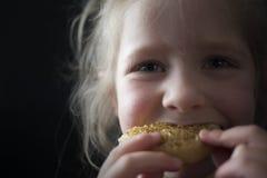 Meisje die een beschuitbol eten Stock Foto's