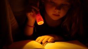 Meisje die een boek in bed lezen Sluit omhoog stock video