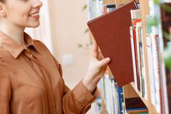 Meisje die een boek in bibliotheek nemen Stock Fotografie