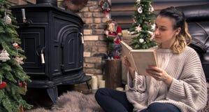 Meisje die een boek in een comfortabele huisatmosfeer lezen dichtbij de open haard stock foto's
