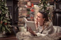 Meisje die een boek in een comfortabele huisatmosfeer lezen dichtbij de open haard stock afbeeldingen