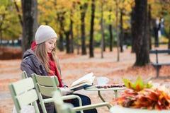 Meisje die een boek in een openluchtkoffie lezen Royalty-vrije Stock Fotografie