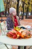 Meisje die een boek in een openluchtkoffie lezen stock afbeelding