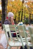 Meisje die een boek in een openluchtkoffie lezen Stock Fotografie