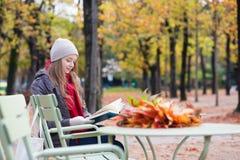 Meisje die een boek in een openluchtkoffie lezen Stock Afbeeldingen