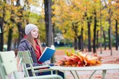 Meisje die een boek in een openluchtkoffie lezen Stock Foto's