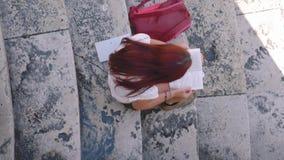 Meisje die een boek op marmeren treden lezen, hoog-hoek, schuine standschot, Italië stock videobeelden